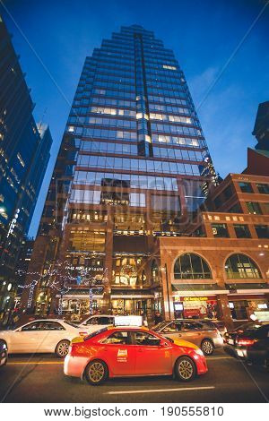 TORONTO, CANADA. December 26, 2014: City Life, Skyscraper and Urban Traffic in Downtown Toronto, Canada. A tall building with crystal glass. At night.