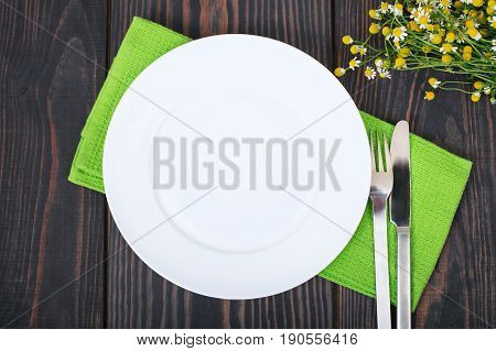The knife fork and white plate on a green napkin on a wooden background.