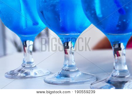 Restaurants, bars, cocktails backgrounds concept. Shot of a glass of alcohol on a countertop. Cropped shot of three glasses of blue cocktails on the table.