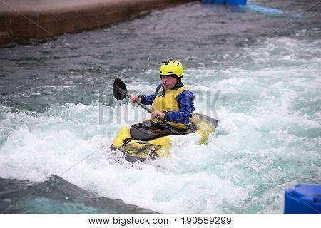 Man In Kayak Paddling Upstream In Fast Flowing Water