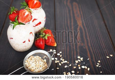 Healthy breakfast: overnight oats with fresh strawberries in a glass jar.