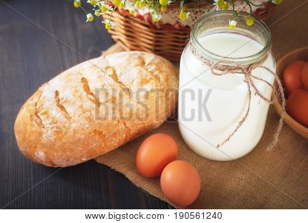 Breakfast from farm products: eggs milk fresh bread on a wooden table.