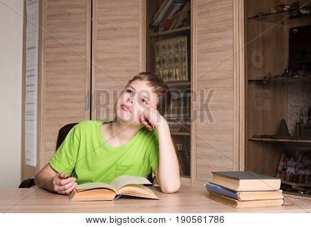 Education and school concept. Teen boy reading a book at home.