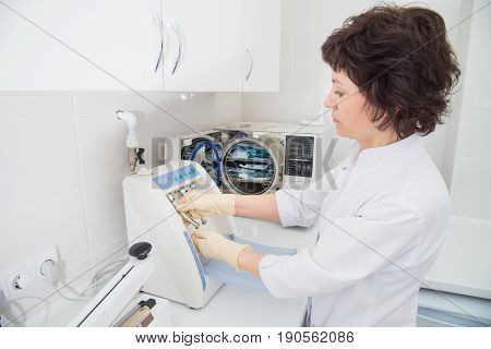 Instrument sterilization and cleaning in dentistry, nurse using automatic instrument maintenance equipment.