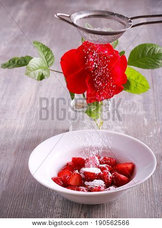 Sliced strawberry and icing powder sifting over