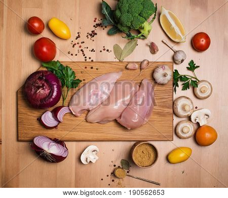 Raw chicken breasts. Fresh chicken meat on wooden cutting board on wooden table with fresh organic vegetables prepared for cooking. Top view. Rustic style.