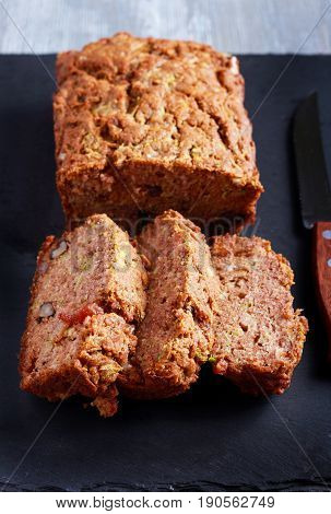 Courgette loaf with sultana and nuts sliced on board