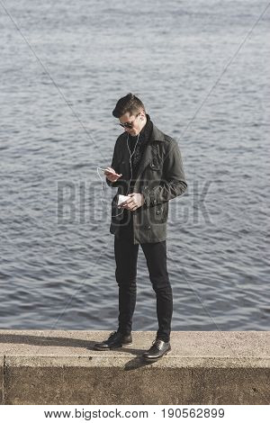 handsome man listening to music. man in sunglasses with music player. young man choosing music track near water. listening to music in earbuds