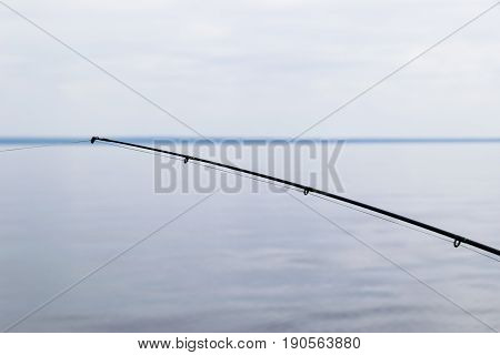Boat fishing rod with the line over a beautiful cloudy seascape