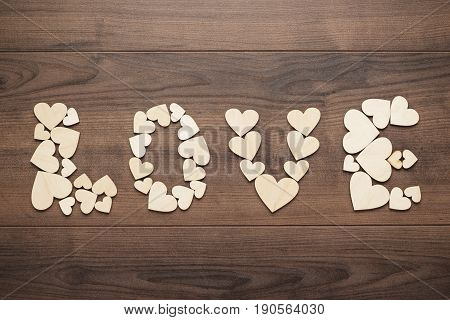 word love made up with cutout hearts. word love on the brown table. wooden hearts forming word love. love concept