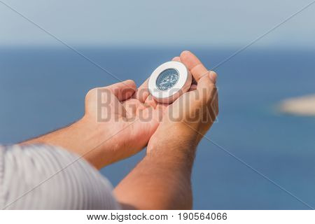 Close up of male hands holding compass outdoors