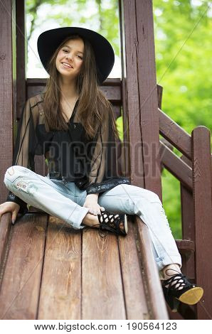 A girl in a hat sits in a wooden pergola in the forest.