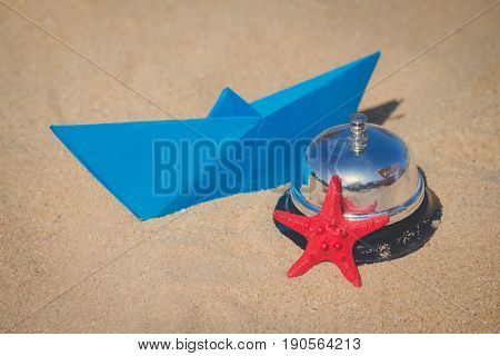 Summertime objects concept. Paper boat sea star and service bell on sandy beach