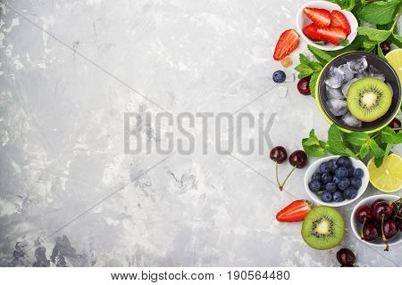 Ingredients healthy diet family meals: fresh juicy fruits and berries with mint and ice to prepare a healthy summer desserts, refreshing drinks, for adding to cereals, filling lunch boxes, for making smoothies on a light marble background. Top view