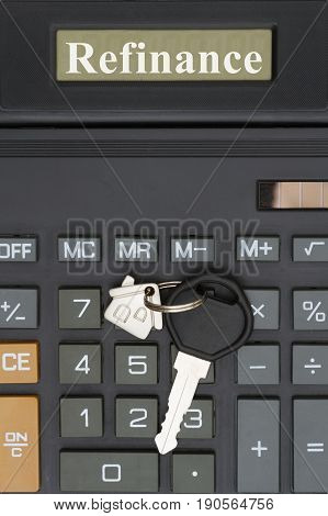 Refinance text on the display of a close-up of a calculator with a house key