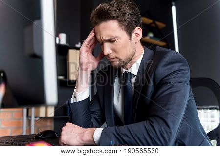 Feeling ill. Portrait of exhausted gloomy pessimistic businessman sitting at table in office and holding his head while expressing pain