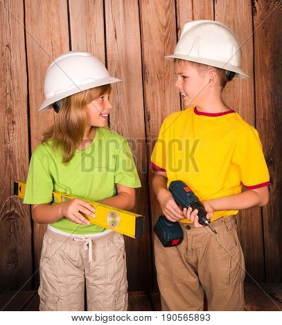 Smiling children in hardhats with tools on wooden background looking at each other. Renovation and construction concept.