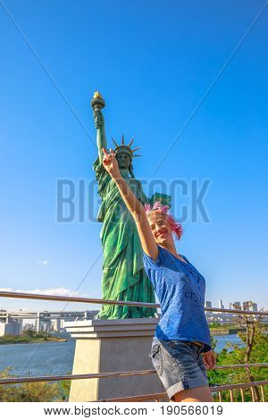 Happy tourist woman enjoying indicating Statue of Liberty, icons of Odaiba Island in Tokyo, Japan. Female lifestyle smiling while on a trip out of Tokyo in popular Odaiba. Summer vacation in Japan.