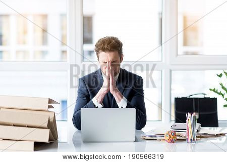 Need more time. Portrait of exhausted cheerless depressed man holding his head and expressing hopelesses. He is sitting in office while surrounded by folders