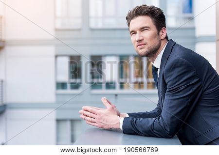 Modern businessman. Portrait of confident young man in suit is leaning on parapet and looking away thoughtfully while standing outdoors on balcony with cityscape in the background. Copy space in the left side
