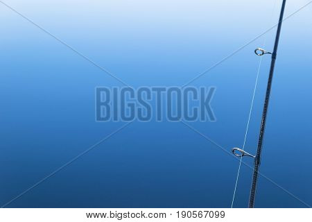 Fishing on the boat with trolling rod and reel. Blue sea background