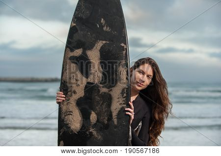 Sexy California surfer girl peeking out from behind black surf board at beach.
