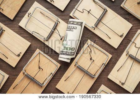 business risks concept of many mousetraps surrounding one hundred dollar bill. business risks concept on brown table. business risks concept on wooden background. business risks conceptual image.