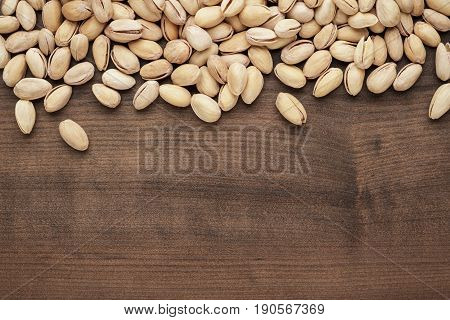 many pistachios on the brown table. pistachios background. roasted pistachios on wooden back. photo of roasted pistachios with copy space