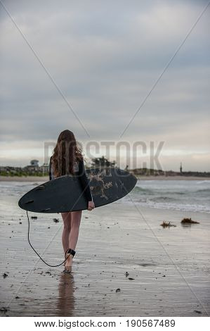 Sexy California surfer girl walking along beach shoreline at dawn.