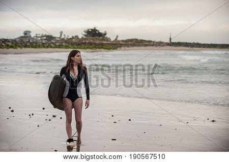 Sexy California surfer girl holding surf board while walking along shore.