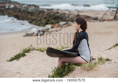 Sexy California surfer girl holding surf board on lap looking ahead.