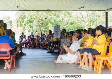 Alofi, Niue - May 27, 2017; Niuean primary children in open air school assembly under cover of roof