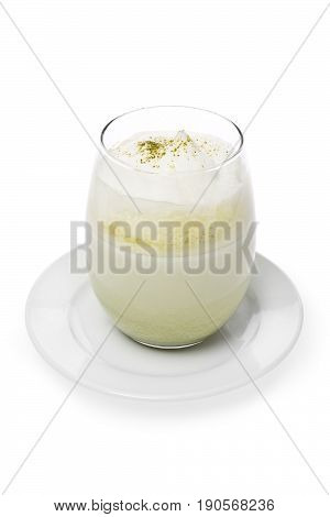 Matcha green tea latte in a glass against a white background.