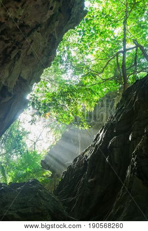 Sun streaming in from above in between walls of coral formation of narrow steep Anapala Chasm Niue.