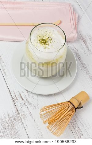 Matcha tea latte in a glass on a sauce next to a pink napkin and a bamboo whisk and spoon.