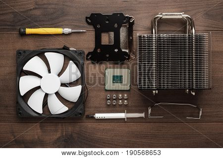 central processing unit for desktop computer and heat sink with cooling fan. computer cpu on the wooden table. building high-performance computer concept. computer cpu installation process