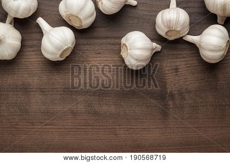 many fresh garlic on the brown table. garlic background. fresh garlic on wooden back. photo of garlic with copy space