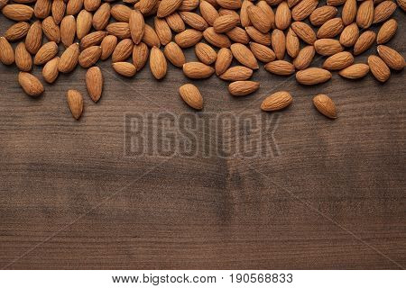 many almond seeds on the brown table. almond seeds background. almond seeds on wooden back. photo of almond seeds with copy space