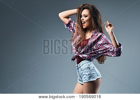 Sexy young girl with disheveled long chestnut hair wearing high waist jeans shorts and oversized knotted red and blue plaid shirt enjoys herself dancing on dark grey background.