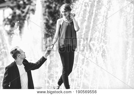 Couple in love next to the fountain on a sunny day. Black and white photo.