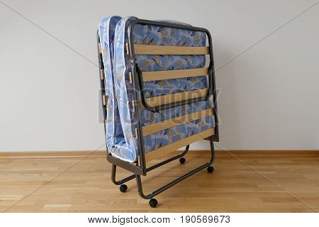 A folding bed in front of a white wall an a blue mattress