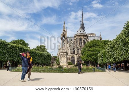 Paris, France - May 11, 2017: Tourists taking a selfie photo at the famous church Notre Dame