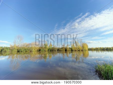 An autumn view of the lake. The sky with rare clouds and trees are reflected in the calm water.