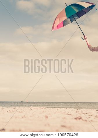 Weather rain protection concept. Woman hand holding colorful umbrella on beach sunny day and clear blue sky