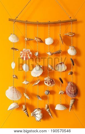 A wind chime with shells on a yellow background on a stick