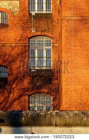 The outside view of an old and abandoned jail in Berlin during sunset