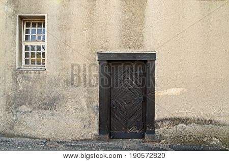 The photograph shows the old, wooden door. They are of dark brown. They have decorative metal ferrules of the black colour of metal painted. They are settled in the plastered wall. They are it is an outside door. There is a day.
