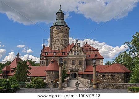 The photograph shows the historic Czocha castle located in Forest in south-west Poland. There is a sunny day, the sky is lightly clouded. Around the castle tall trees grow. He is leading a stone bridge to the castle.
