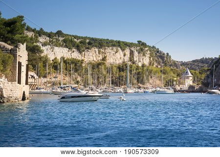 CASSIS,FRANCE-AUGUST 10,2016:The port of inside a creek near Cassisa French village with colorful boats moored and the lighthouse during a summer day.