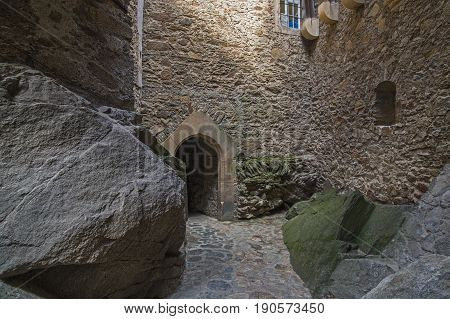 The photo shows a narrow passage on the one hand bounded by basalt rock, on the other hand bounded by a castle wall. It has pavement made of paving stones. It leads to a wall where there is an arched passage leading further. This passage is an architectur